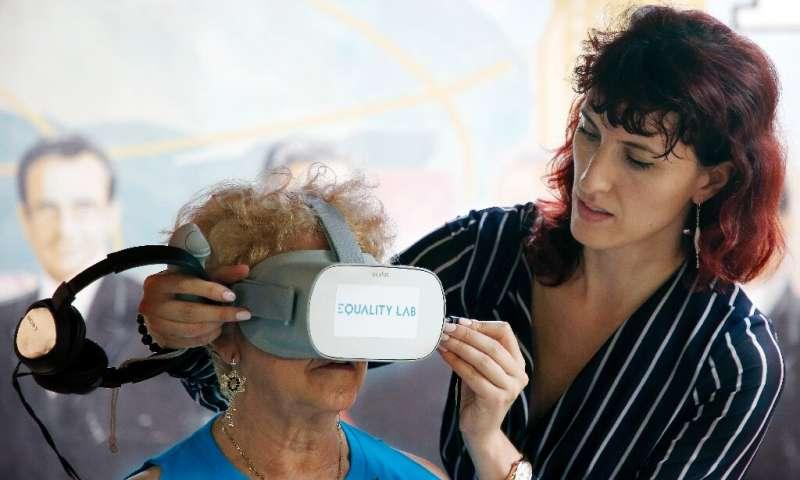 Alexandra Ivanovitch (D) assiste Nidia Silva (L) avec le casque de réalité virtuelle dans le quartier de Little Havana à Miami, Floride